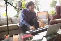 Jeune homme endisquer, jouant le piano clavier dans appartement — Photo de stock