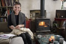 Portrait smiling, confident woman knitting by fireplace in living room — Stock Photo