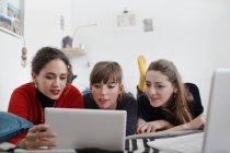 Young women friends sharing digital tablet on bed — Stock Photo