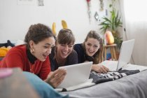 Young women friends hanging out, using digital tablet and laptop on bed — Stock Photo