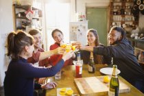 Happy young adult friends toasting cocktails at apartment kitchen table — Stock Photo