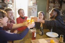 Young adult friends toasting cocktails at apartment kitchen table — Stock Photo