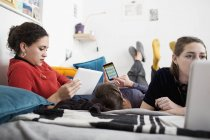 Young women friends hanging out, using smart phone, digital tablet and laptop on bed — Stock Photo