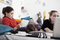 Молоді жінки друзі гуляти, використовуючи смарт-телефон, цифровий планшет і ноутбук на ліжку — стокове фото