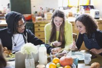 Young roommate friends using digital tablet at breakfast table — Stock Photo