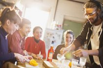 Young adult friends making cocktails at kitchen table — Stock Photo
