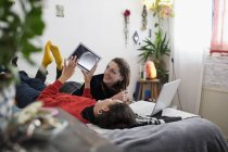 Young women friends relaxing, using digital tablet and laptop on bed — Stock Photo