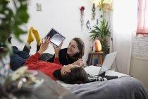 Amis de jeunes femmes se détendre, à l'aide de tablette numérique et l'ordinateur portable sur lit — Photo de stock