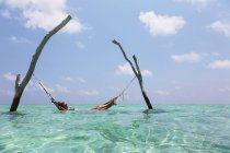 Woman laying in hammock over tranquil ocean, Maldives, Indian Ocean — Stock Photo