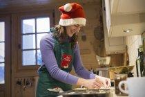 Lächelndes Teenie-Mädchen in Weihnachtsmütze backen in der Küche — Stockfoto