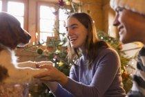 Glückliches Geschwisterpaar spielt mit Hund im weihnachtlichen Wohnzimmer — Stockfoto