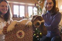 Мать и дочь, играя с собакой в Рождественский подарок коробку — стоковое фото