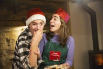 Playful brother and sister eating Christmas cookies — Stock Photo