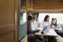 Сімейного відпочинку, їдять і використовуючи цифровий планшетний в будинок — стокове фото