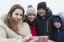 Snow falling on smiling family taking selfie — Stock Photo