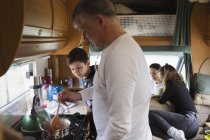 Family cooking in motor home — Stock Photo