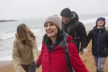 Snow falling over happy family on winter beach — Stock Photo