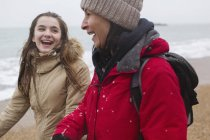 Happy mother and daughter walking on snowy beach — Stock Photo