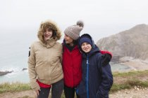 Portrait happy family in warm clothing standing on cliff overlooking ocean — Stock Photo