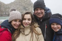 Snow falling over smiling family posing in warm clothing — Stock Photo