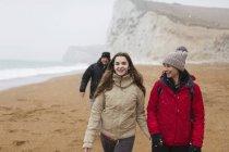 Affectueuse mère et fille marchant sur la plage enneigée d'hiver — Photo de stock