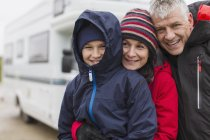 Portrait affectionate family in warm clothing hugging outside of motor home — Stock Photo