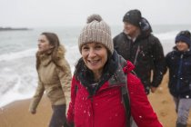 Portrait smiling woman in warm clothing with family on snowy winter ocean beach — Stock Photo