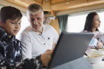 Father and son using digital tablet in motor home — Stock Photo