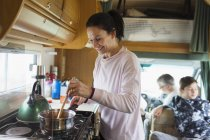 Femme souriante, cuisine en camping-car — Photo de stock
