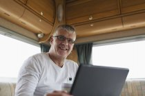 Smiling, confident man drinking coffee and using digital tablet in motor home — Stock Photo
