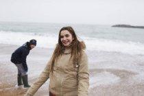 Lächelndes Teenager-Mädchen am winterlichen Ozeanstrand — Stockfoto