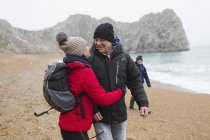 Affectionate, happy couple in warm clothing on snowy winter beach — Stock Photo