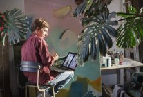 Männliche Künstler malen und mit Laptop im Kunstatelier — Stockfoto