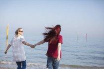 Affectueux couple de lesbiennes tenant la main sur la plage ensoleillée de l'océan — Photo de stock