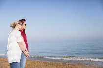 Casal lésbico afetuoso de mãos dadas na praia ensolarada do oceano — Fotografia de Stock