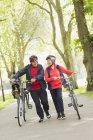 Активные старший пара прогулки велосипеды в парке — стоковое фото
