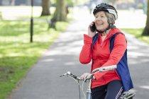 Donna anziana attiva che parla al cellulare in bicicletta nel parco — Foto stock