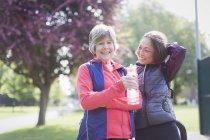 Портрет уверенный в себе активная старшая бегунья друзья питьевой воды в парке — стоковое фото