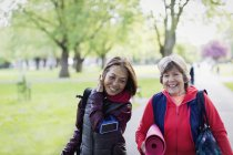 Active senior women friends with yoga mat walking in park — Stock Photo