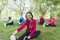 Portrait smiling, confident active senior woman stretching in park — Stock Photo