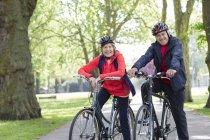 Портрет, улыбаясь, уверенно активные Пожилые супружеские пары, езда велосипеды в парке — стоковое фото