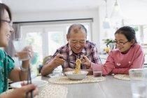 Grand-père et petite-fille partageant des nouilles à table — Photo de stock