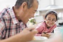 Lächelnder Großvater und Enkelin essen am Tisch — Stockfoto