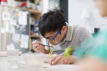 Man eating noodles with chopsticks at table — Stock Photo