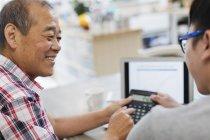 Sohn hilft Senior-Vater beim Bezahlen von Rechnungen am Laptop — Stockfoto