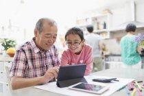 Nonno e nipote utilizzando tablet digitale in cucina — Foto stock