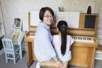 Porträt lächelnde Mutter sitzt mit Tochter beim Klavierspielen — Stockfoto