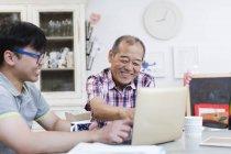 Сын помогает старшему отцу использовать ноутбук на кухне — стоковое фото