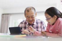 Діда і онука забарвлення і використовуючи цифровий планшетний — стокове фото