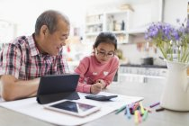 Grandfather and granddaughter coloring and using digital tablet in kitchen — Stock Photo